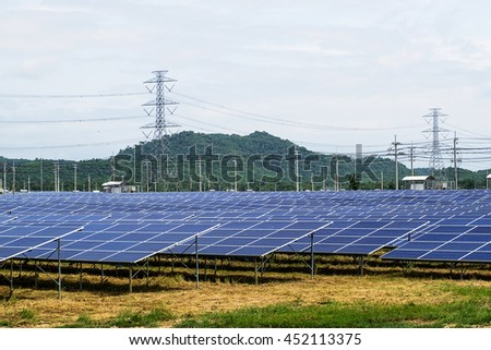 Solar Panel With High Voltage Tower in Background - stock photo