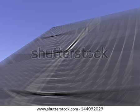 Solar panel with seeming orbital trails, caused by radial blur, under clear blue sky - stock photo