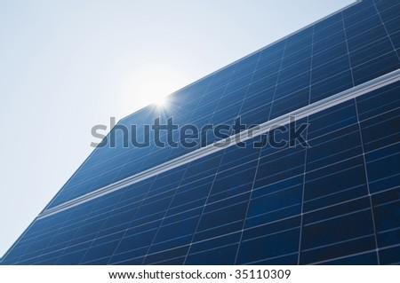 solar panel with sun hitting it - stock photo
