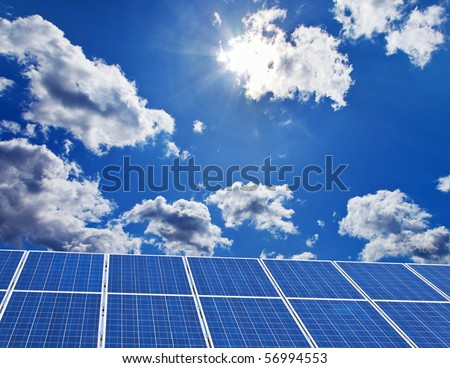 Solar panels against a blue sky with clouds - stock photo