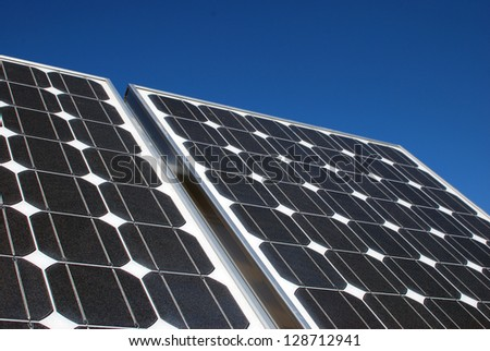 Solar panels against a deep blue sky - stock photo