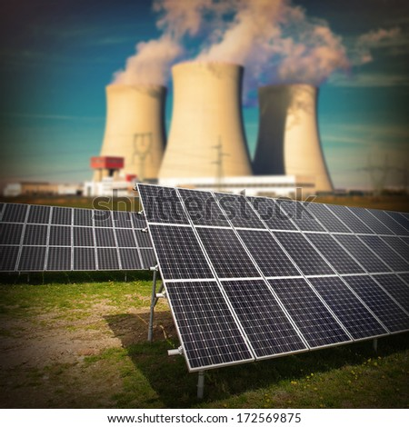 Solar panels against nuclear power plant. Sustainable development and renewable resources concept.  - stock photo