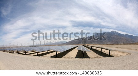 Solar Panels AKA- Photovoltaic Cells in a SOLAR FARM with Wind Turbines in the background collect and produce Electricity from Natural Renewable Resources of the Sun and Wind producing GREEN ENERGY - stock photo