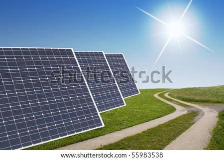 Solar Panels and a snaky path in the green with sun in back - stock photo