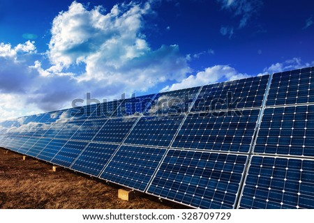 Solar panels and cloudy sky background - stock photo