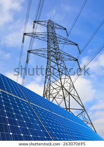Solar panels and electricity pylon against blue sky