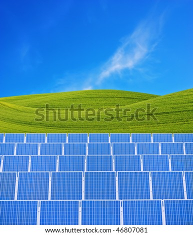 Solar panels and green fields against blue sky. - stock photo