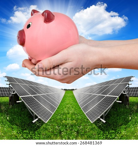 Solar panels and hand holding a pink piggy bank. Concept of saving money. - stock photo