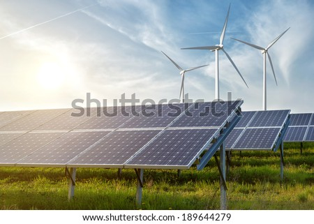 solar panels and wind generators under blue sky on sunset - stock photo