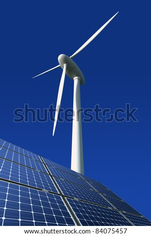 Solar panels and wind turbine against a blue background - stock photo