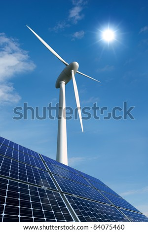 Solar panels and wind turbine against a sunny sky - stock photo