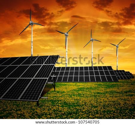 Solar panels and wind turbine in the setting sun - stock photo