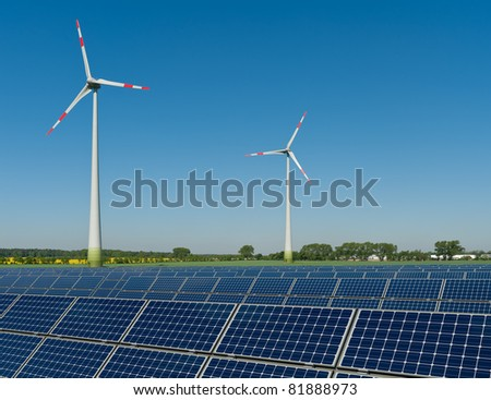 Solar panels and wind turbines against a rapeseed field - stock photo