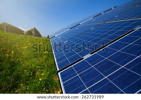 Solar panels, blue sky and green grass in bright sunshine - stock photo