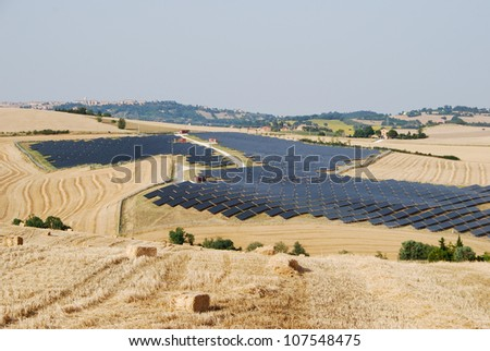 Solar panels for renewable energy with Marche region landscape - Italy - stock photo