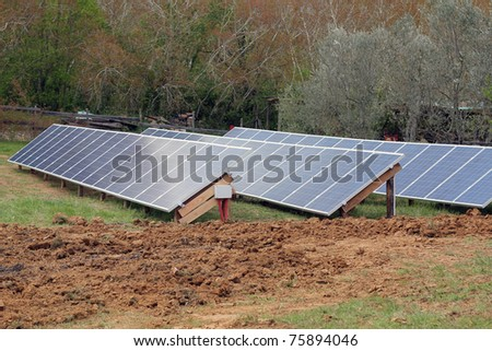 solar panels in a feild in tuscany - stock photo