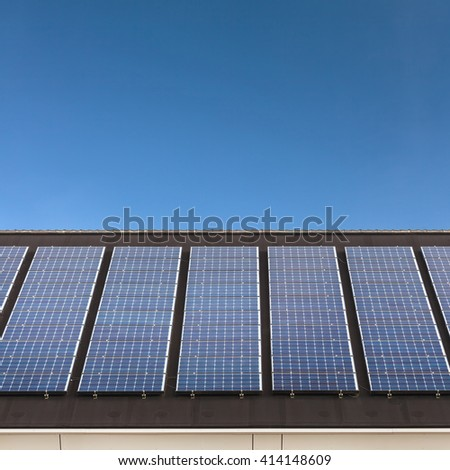 Solar panels in a horizontal row on a roof with a blue sky in the background - stock photo