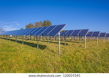 Solar panels in field with blue sky - stock photo