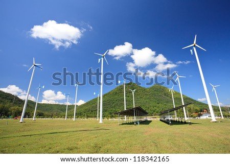 Solar panels in front of wind energy plants - stock photo
