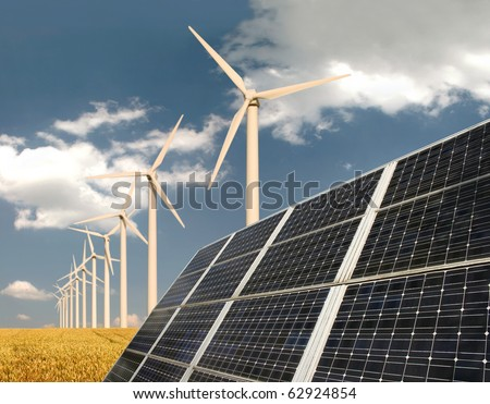 Solar panels in front of wind energy plants and wheat field - stock photo