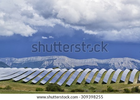 Solar panels lines in the field with big storm cloud in the sky - stock photo