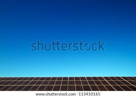 Solar panels lining the horizon, blue sky - stock photo