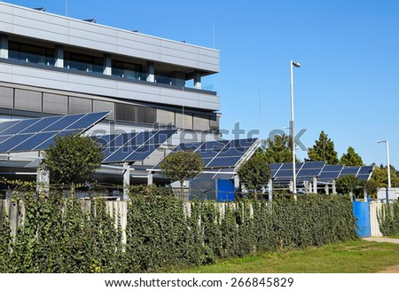 Solar panels next to an office building - stock photo