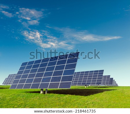 Solar panels on a field under blue sky - stock photo