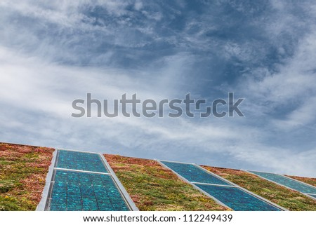 Solar panels on a new roof covered with green and red sedum for isolation and heating - stock photo
