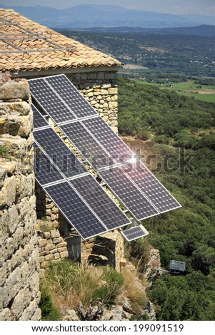 Solar panels on a roof reflecting the sun - stock photo