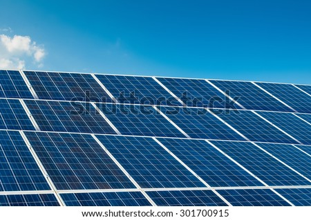 Solar panels on blue sky with copy space and text area - stock photo