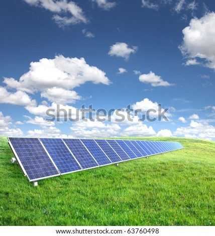 Solar panels on green grass with blue sky - stock photo