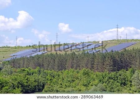 Solar panels on green hill - stock photo