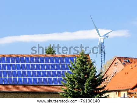 Solar panels on roof of the barn and a windmill behind the farm buildings. Thuringia, Germany - stock photo