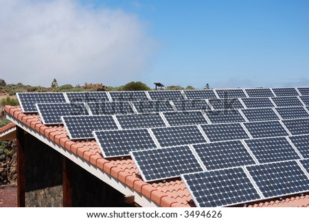solar panels on rooftop, sky with clouds - stock photo