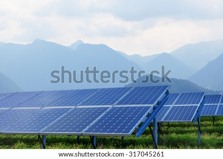 solar panels on summer landscape with mountains on background - stock photo