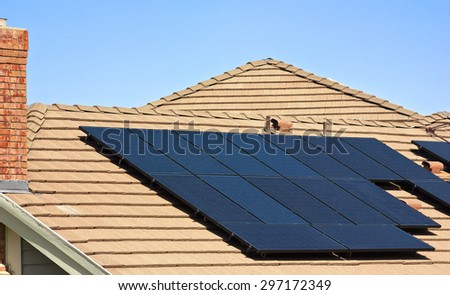 Solar Panels sit on top of a modern roof.  - stock photo