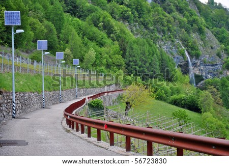 solar panels to produce electricity using the sun's rays to illuminate the mountain road - stock photo
