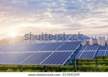 solar panels under sky and clouds with city on horizon. Sunrise - stock photo
