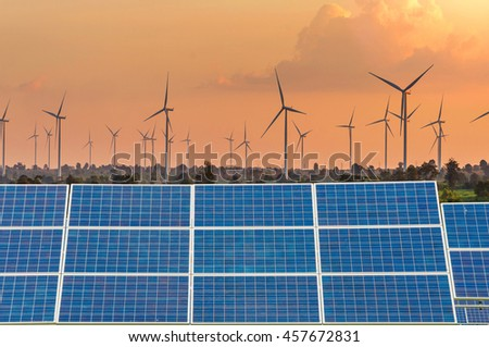 Solar Panels using renewable solar energy in Eco power in wind turbine farm with sunset. - stock photo