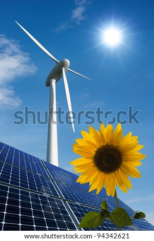 Solar panels, wind turbine and sunflower against a sunny sky - stock photo