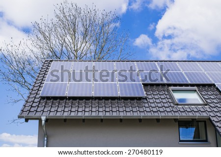 solar panels with blue sky on the house roof - stock photo