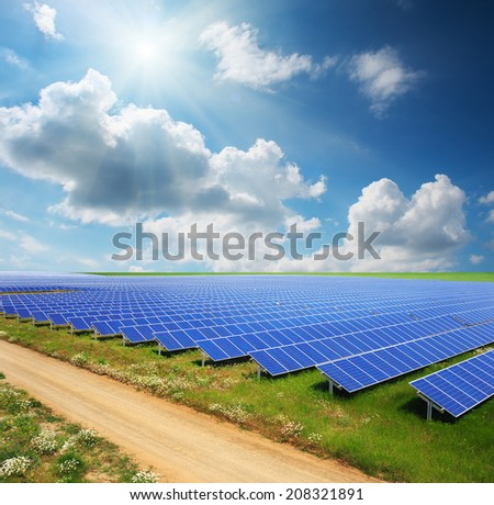 Solar panels with green field and country road - stock photo
