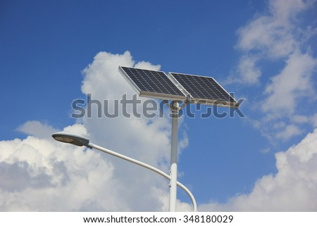 Solar panels with lamp over blue sky