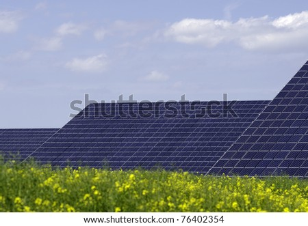 solar panels with rapeseed in the foreground - stock photo