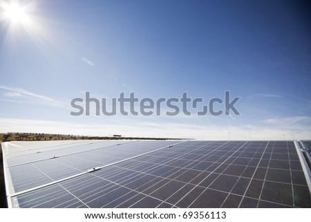 Solar panels with sun overhead - stock photo