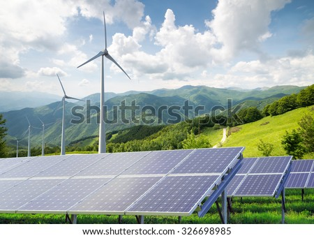 solar panels with wind turbines against mountanis landscape against blue sky with clouds  - stock photo