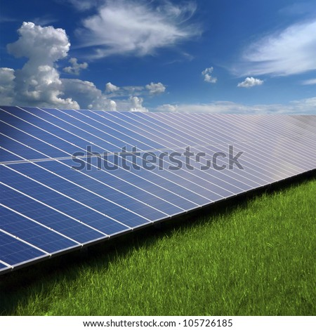 Solar photovoltaic cell panels on green grass under blue sky - stock photo