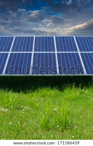 solar photovoltaic cell panels on green grass under cloudy sky - stock photo