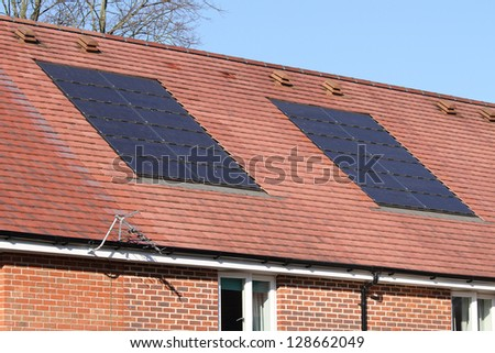 Solar photovoltaic panel array on house roof - stock photo